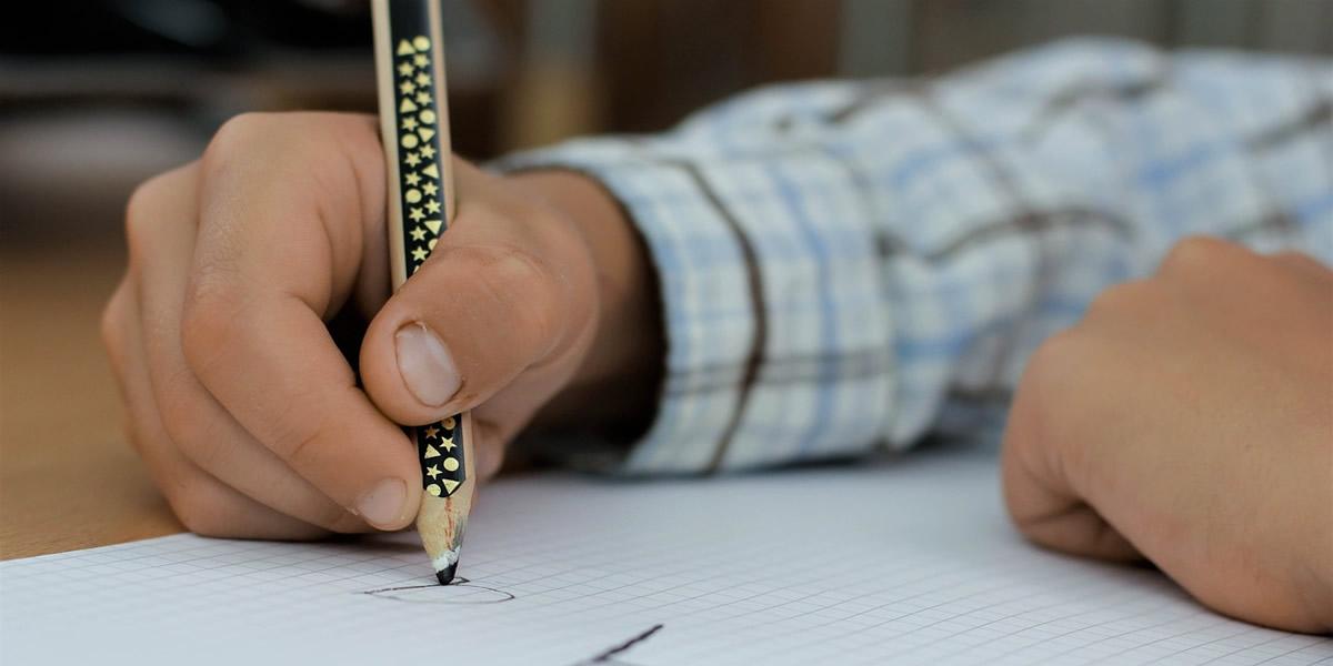 mano di bambino che scrive con la matita