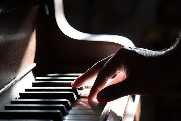 mano sulla tastiera di un pianoforte