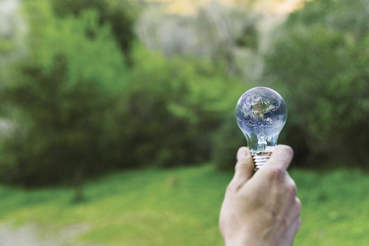 mano che regge una lampadina con all'interno il pianeta Terra