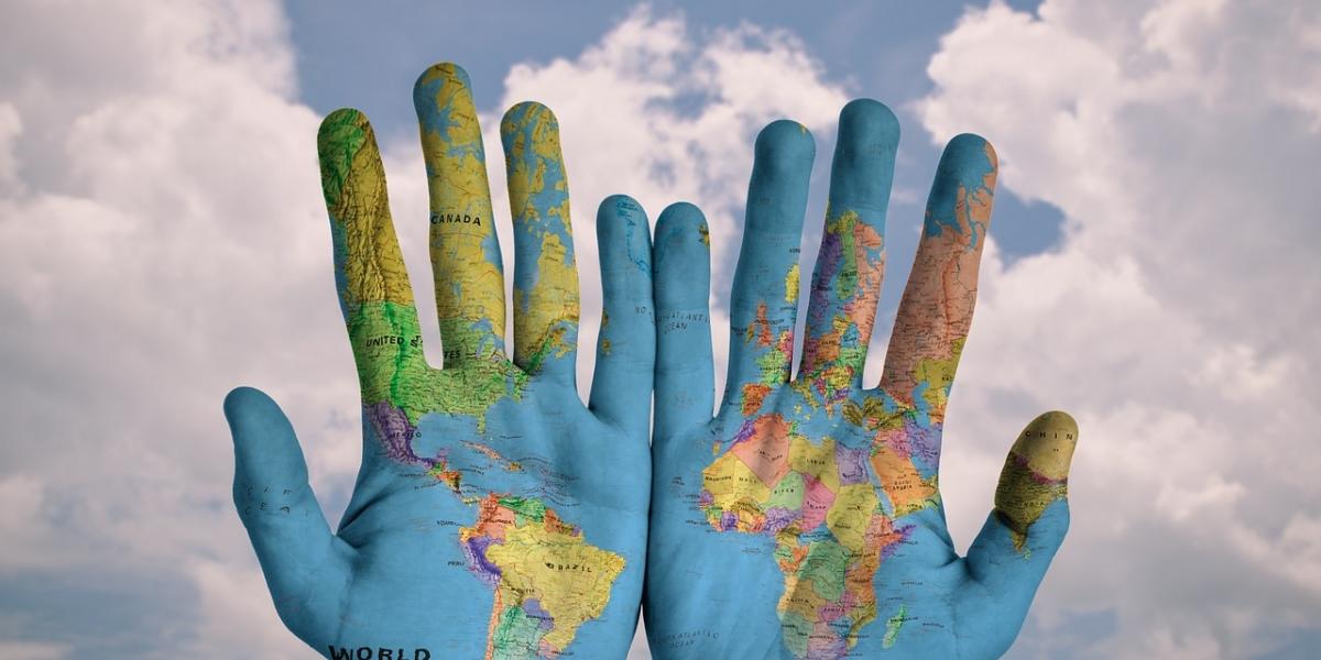 mani con dipinta la mappa del mondo