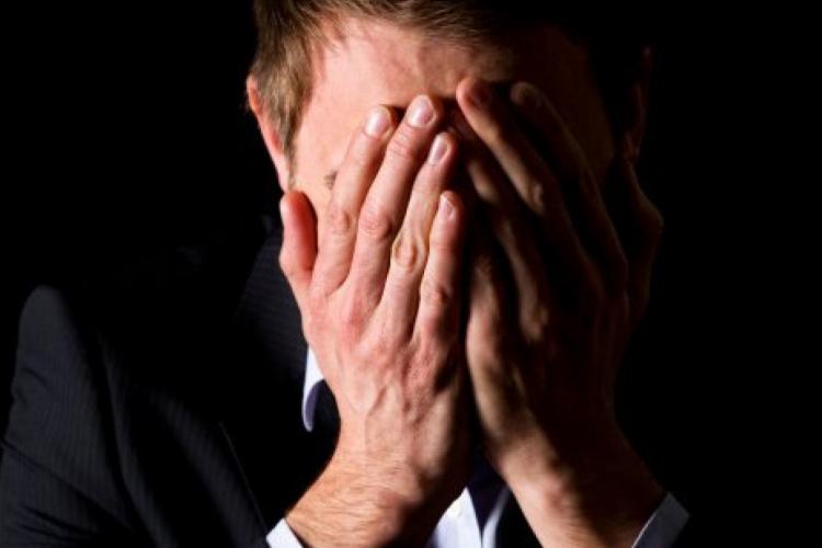 Dettaglio della locandina: uomo che si copre il viso con le mani