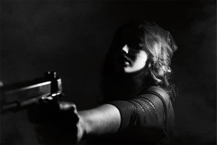Dettaglio della locandina: donna che punta una pistola