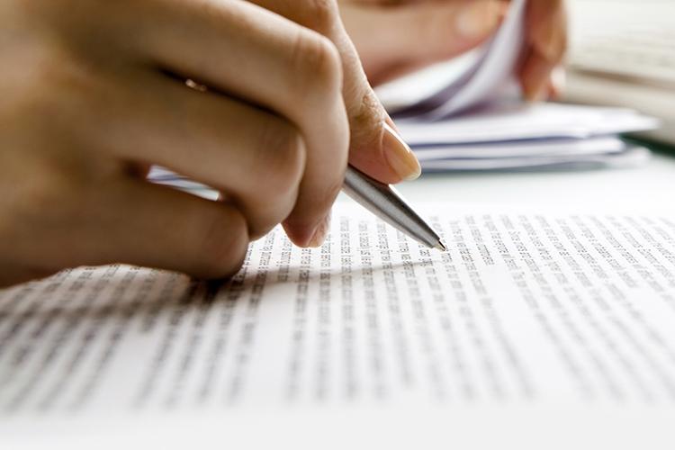 Dettaglio della locandina: mano con la penna che scrive