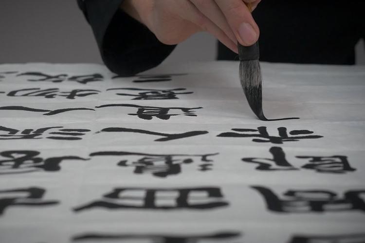 manco che tiene un pennello e traccia caratteri cinesi