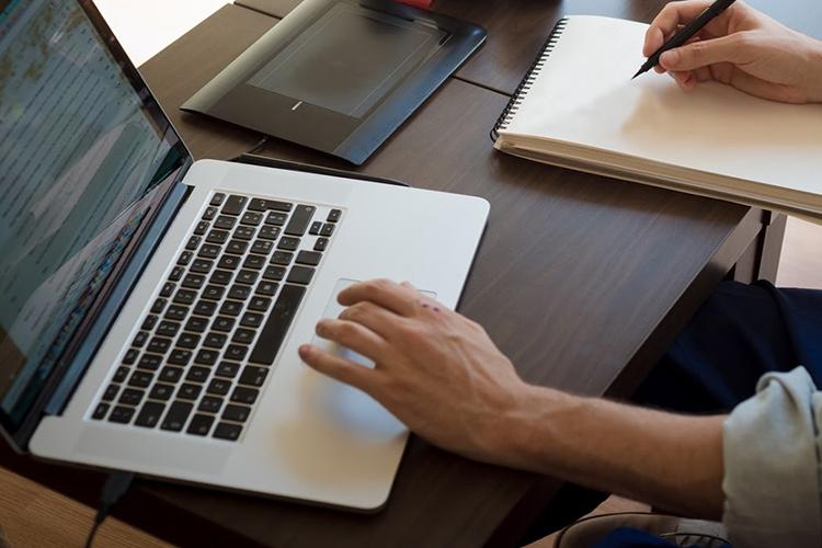 Dettaglio della locandina: uomo che guarda il computer e scrive su carta
