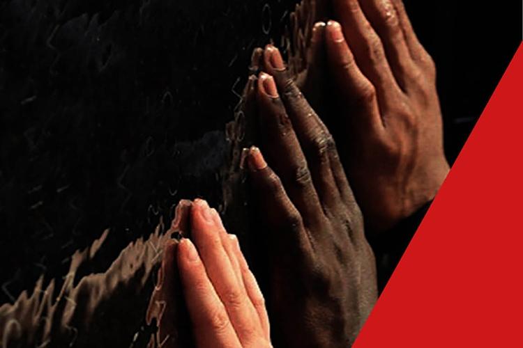 Dettaglio della locandina: mani contro un muro