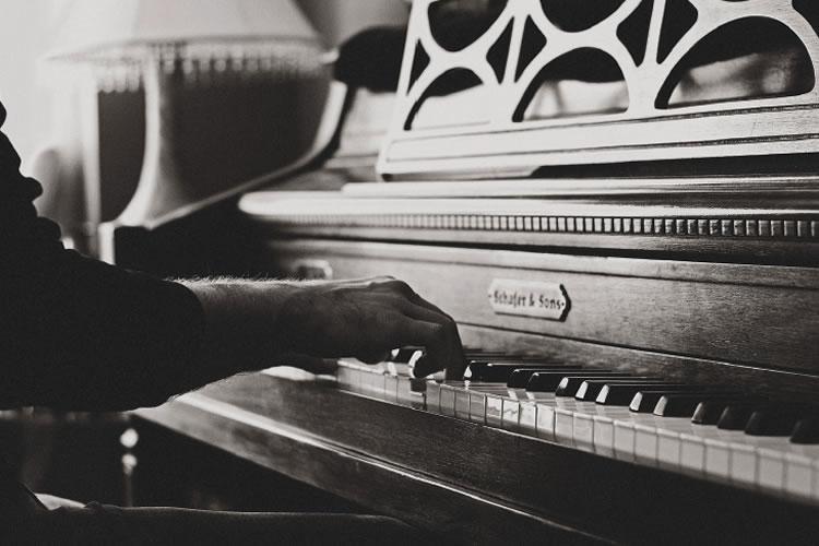 Dettaglio della locandina: mani che suonano un pianoforte