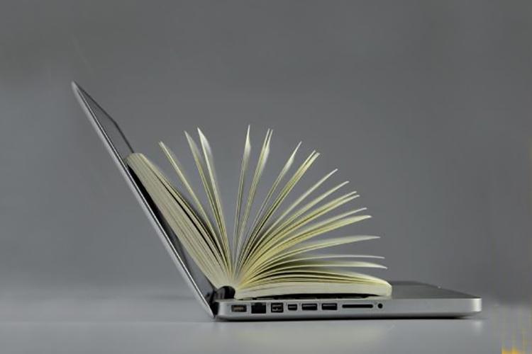 Dettaglio della locandina: libro aperto su computer