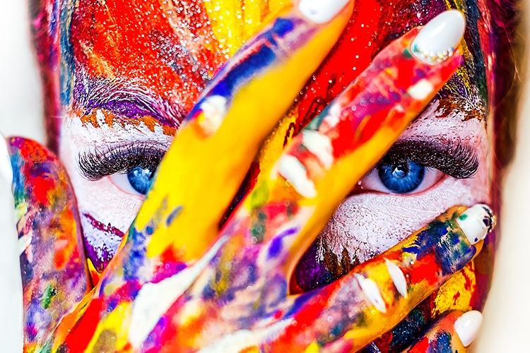 Dettaglio della locandina: volto di donna e mano dipinta di molti colori