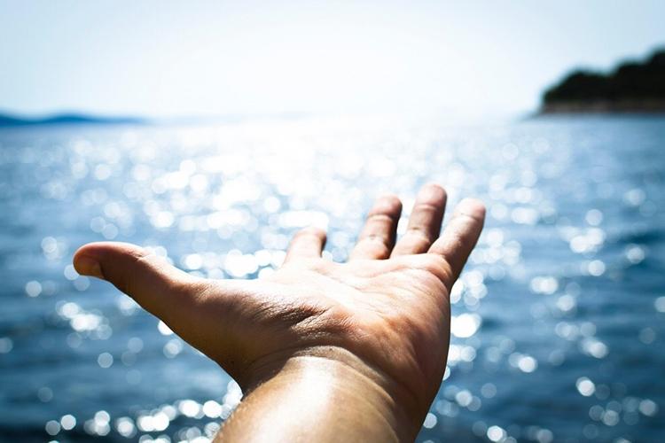 mano protesa verso il mare