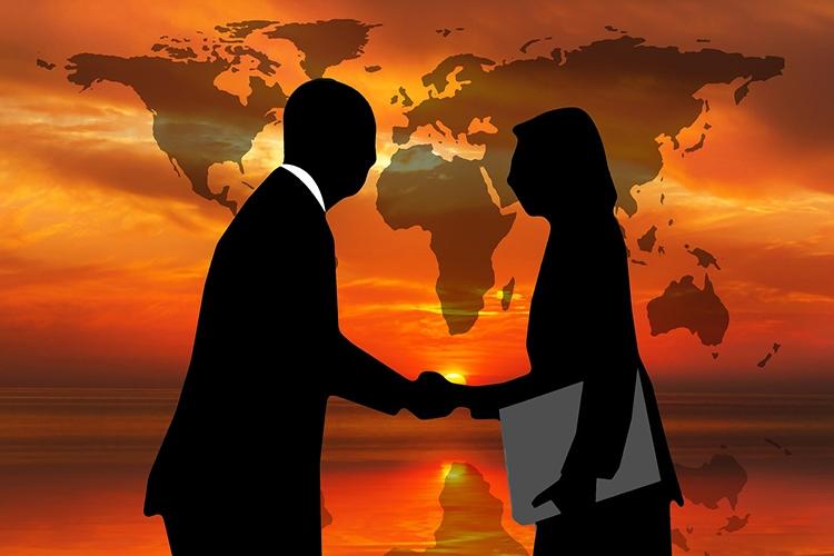 persone che si stringono la mano con una mappa del mondo sullo sfondo