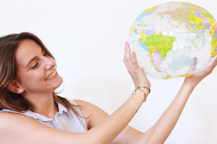 ragazza sorridente che tiene in mano un mappamondo