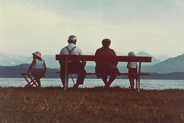 Dettaglio della locandina: persone sedute su una panchina viste di spalle