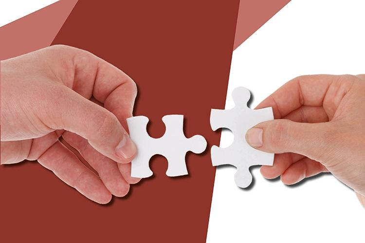 particolare della locandina: due mani che accostano delle tessere di un puzzle