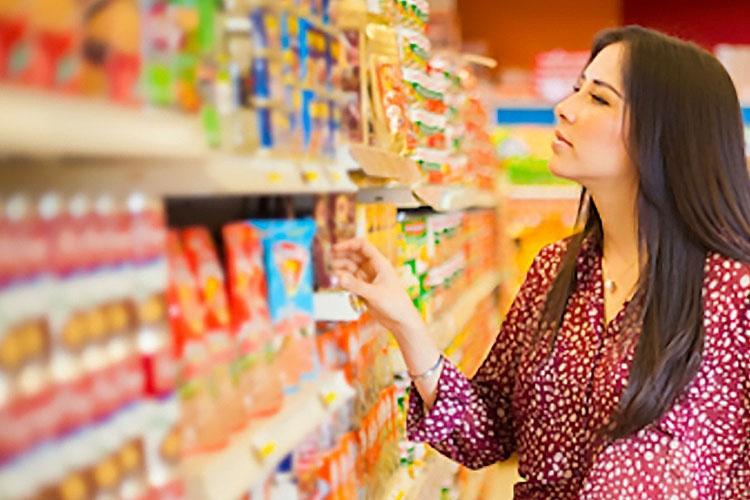 donna che osserva dei prodotti all'interno di un supermercato