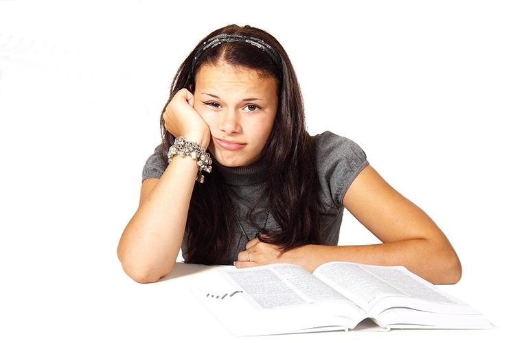 ragazza imbronciata davanti ad un libro