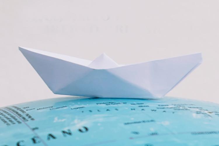 particolare della copetina del libro: barchetta di carta su di un mappamondo