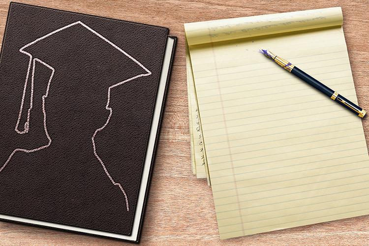 blocco per scrivere con penna e sagoma di laureato