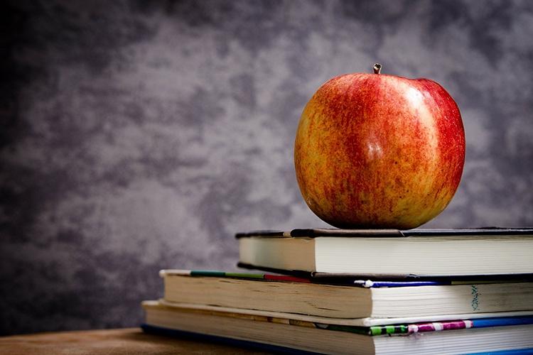 una mela appoggiata su dei libri