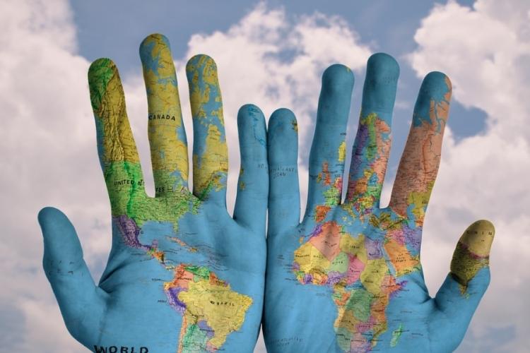 mani su cui è impressa la mappa del mondo