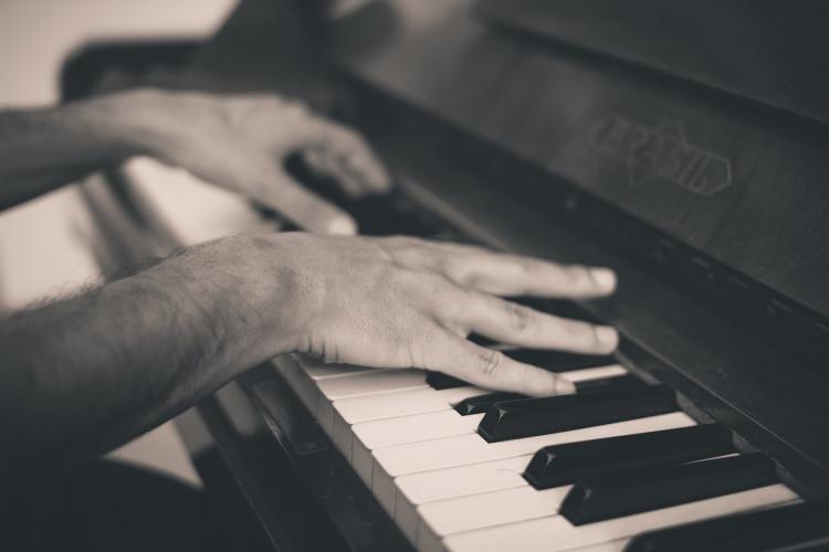 mani che suonano la tastiera di un pianoforte