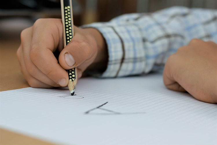 mano di bambino che srive con la matita