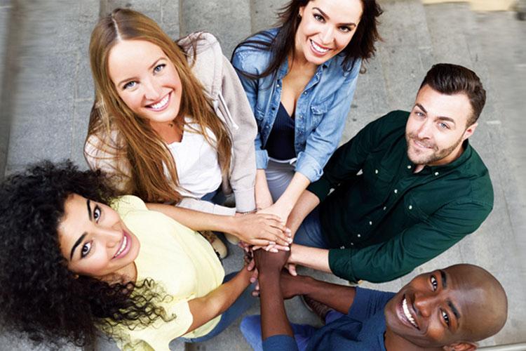 giovani in cerchio con le mani tutte sovrapposte