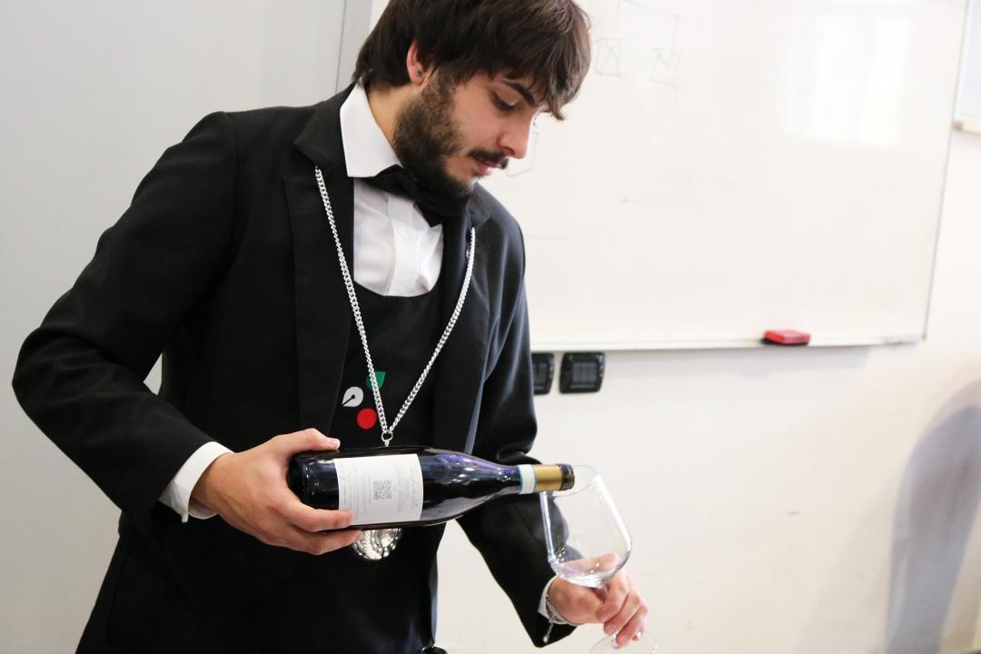 somellier che versa il vino in un bicchiere